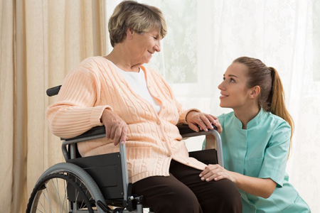 home care provider speaking to an elderly woman in a wheel chair