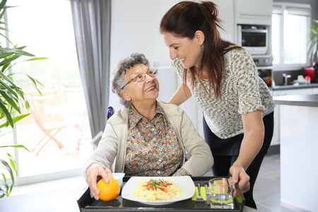 Home care provider giving breakfast to her patient, an elderly woman