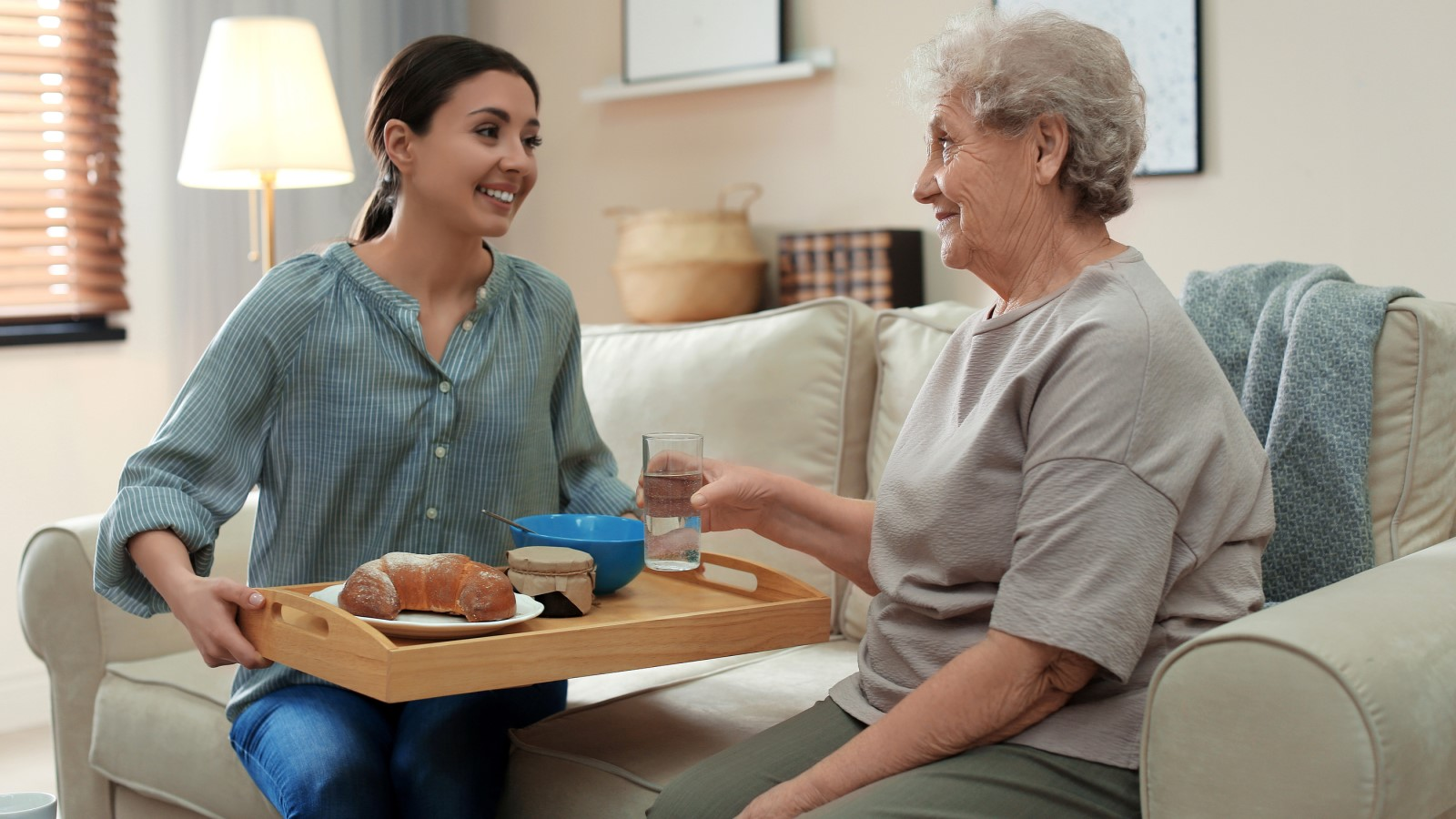 Happy elderly woman getting breakfast from her senior care service provider