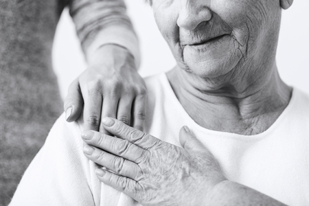 A younger person's hand rests on an older woman's shoulder. The older woman touches the hand with hers.