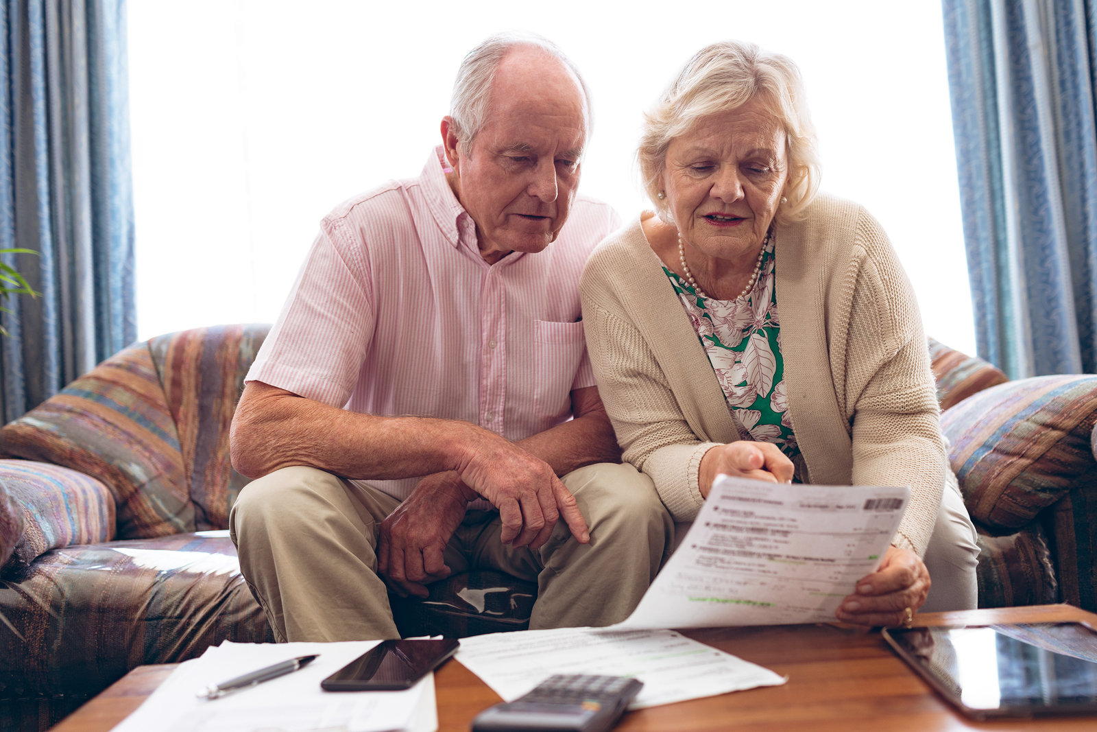 an elderly couple at home with paperwork looking into if Medicare covers home care