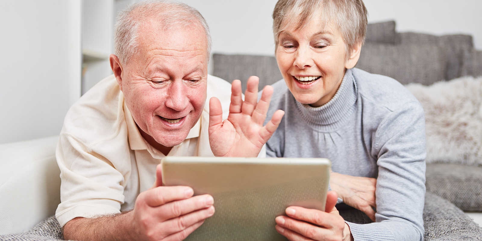 a senior couple waves as they video conference on a laptop with family