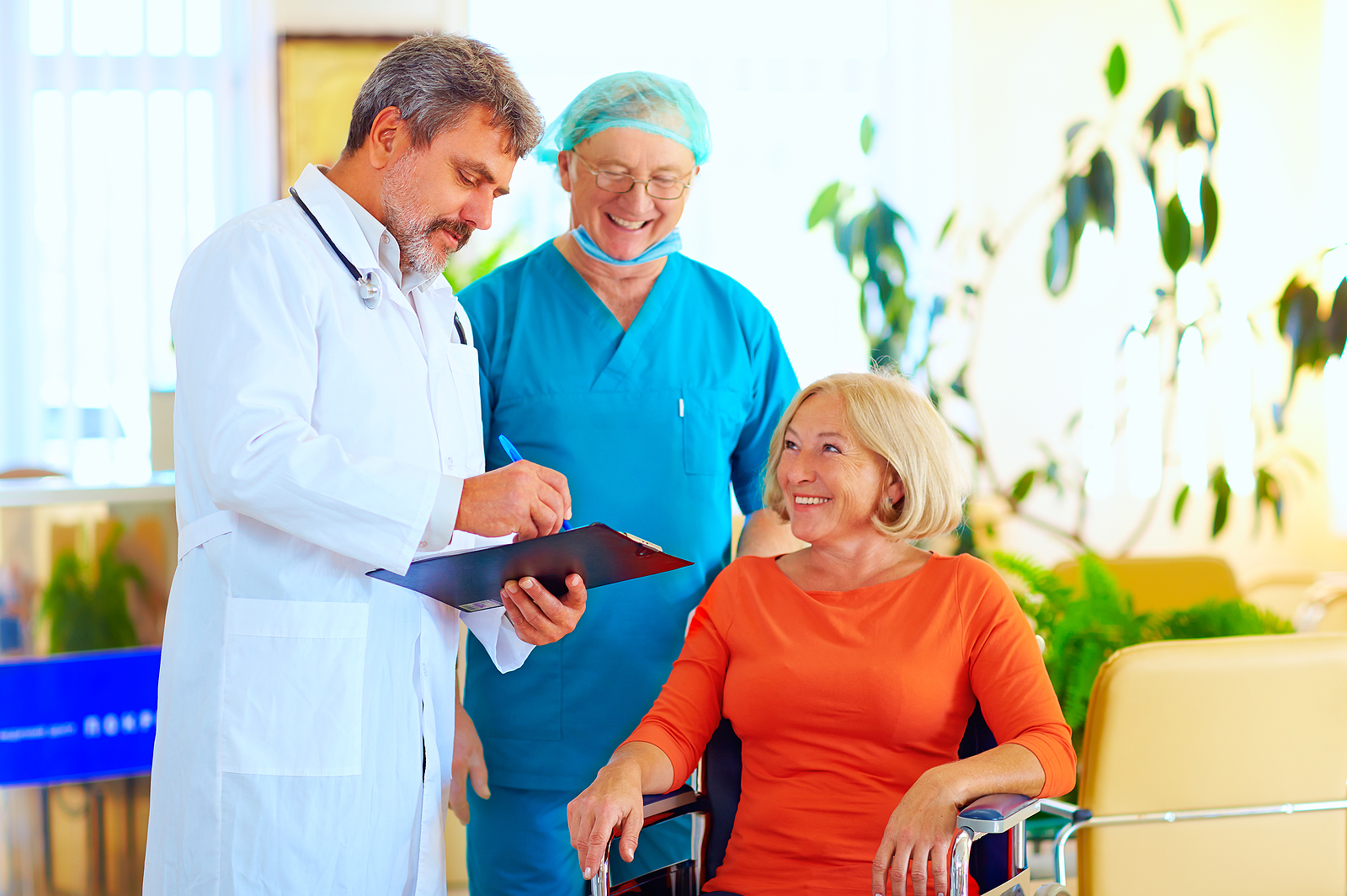 A smiling doctor and surgeon consult a smiling patient about treatment before discharging her from the hospital. Learn about Georgetown Home Care's hospital readmission reduction program.